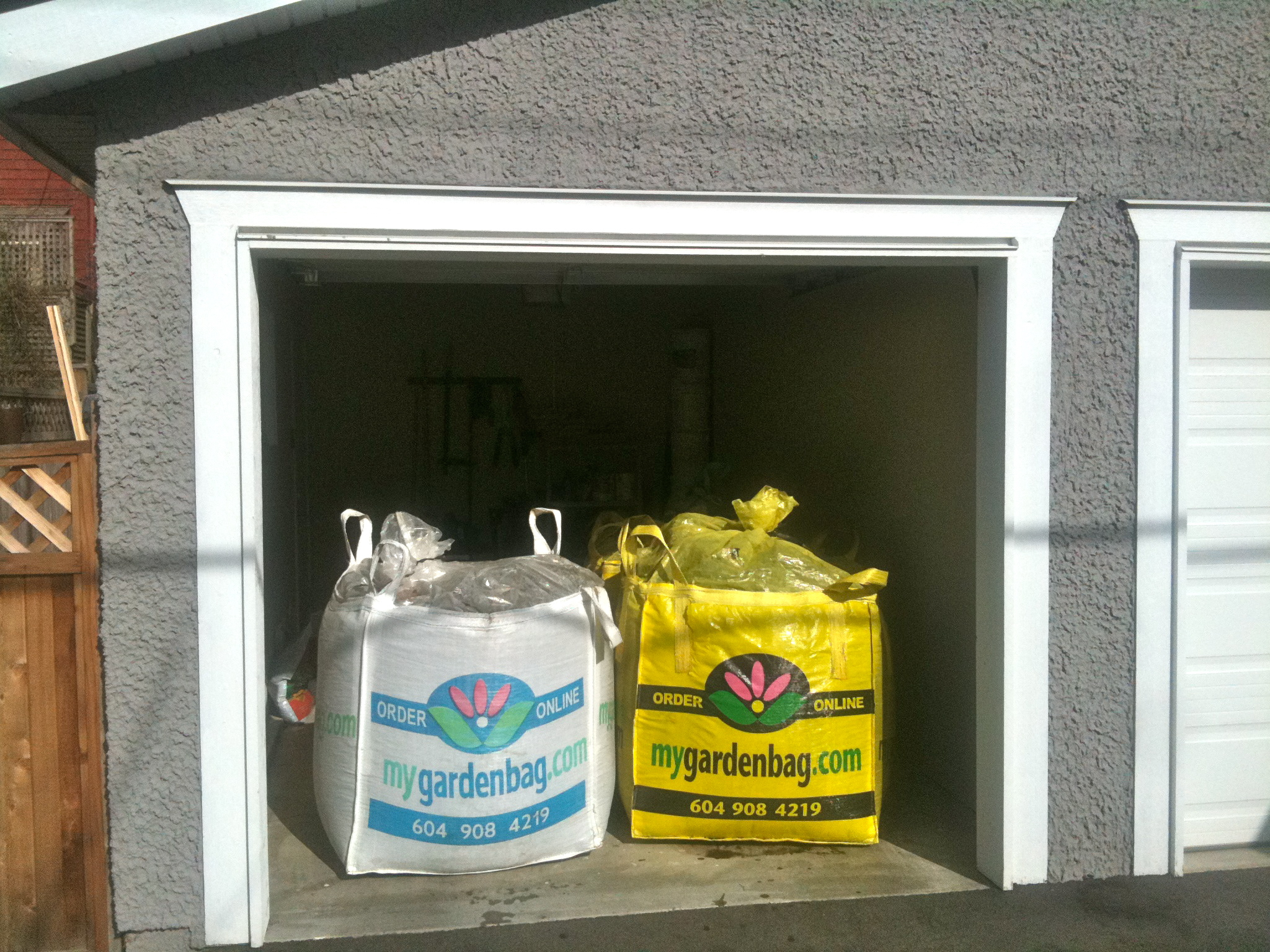 big white bag and big yellow bag full of premium soil